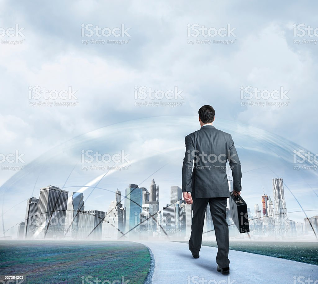 Businessman walking towards protected futuristic city stock photo