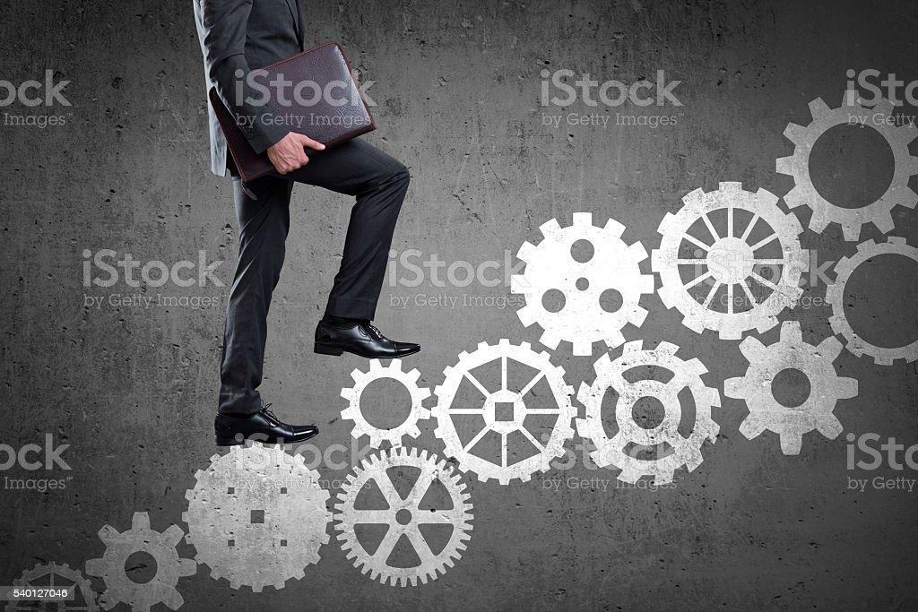 Businessman walking up set of gears stock photo