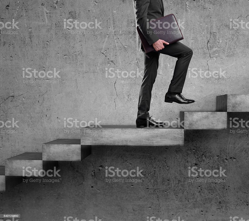 Businessman walking up staircase stock photo