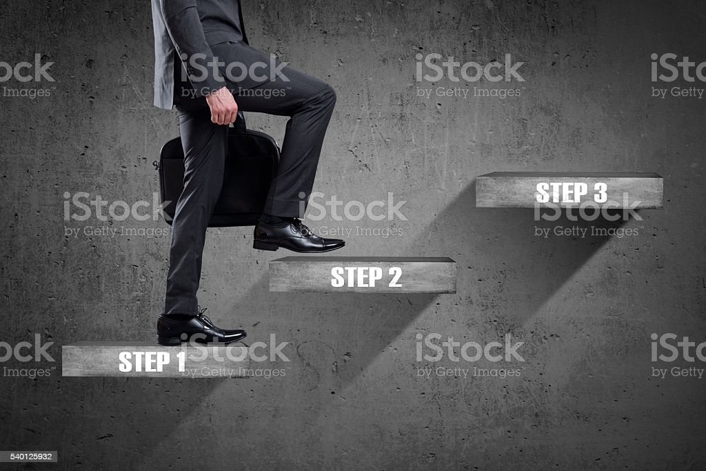 Businessman walking up staircase to successful business steps. stock photo