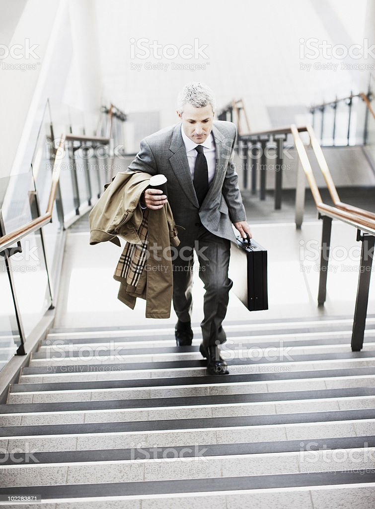 Businessman walking up stairs in train station royalty-free stock photo