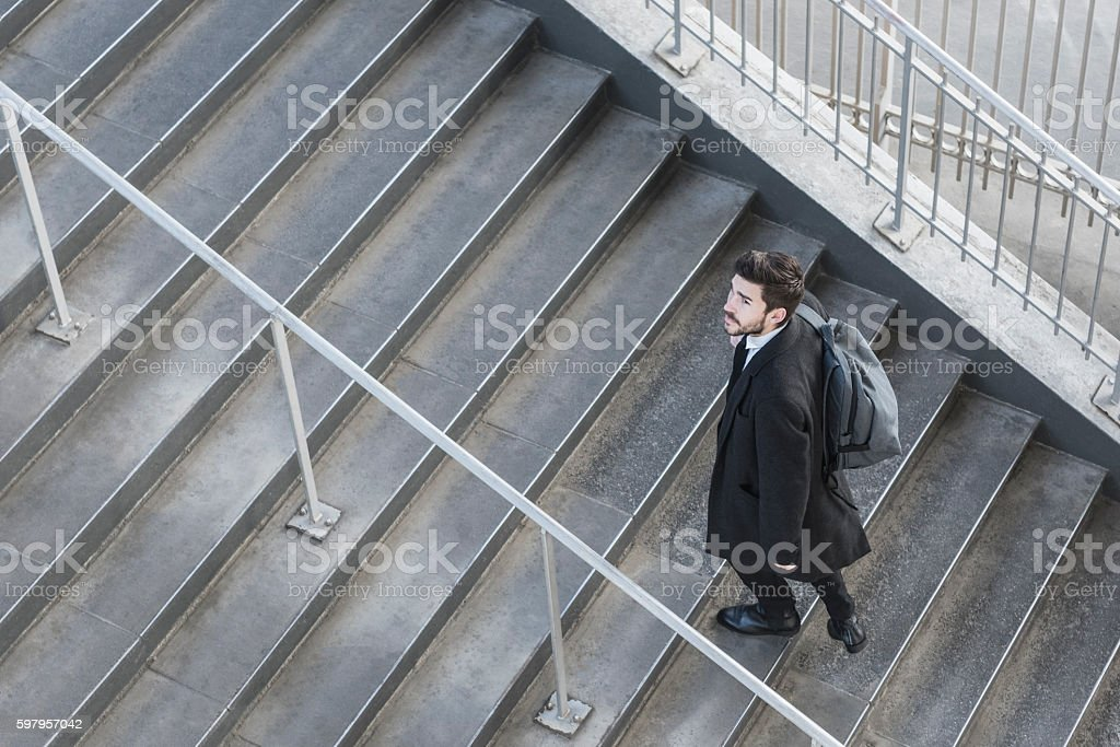 Businessman walking up stairs on work commute stock photo