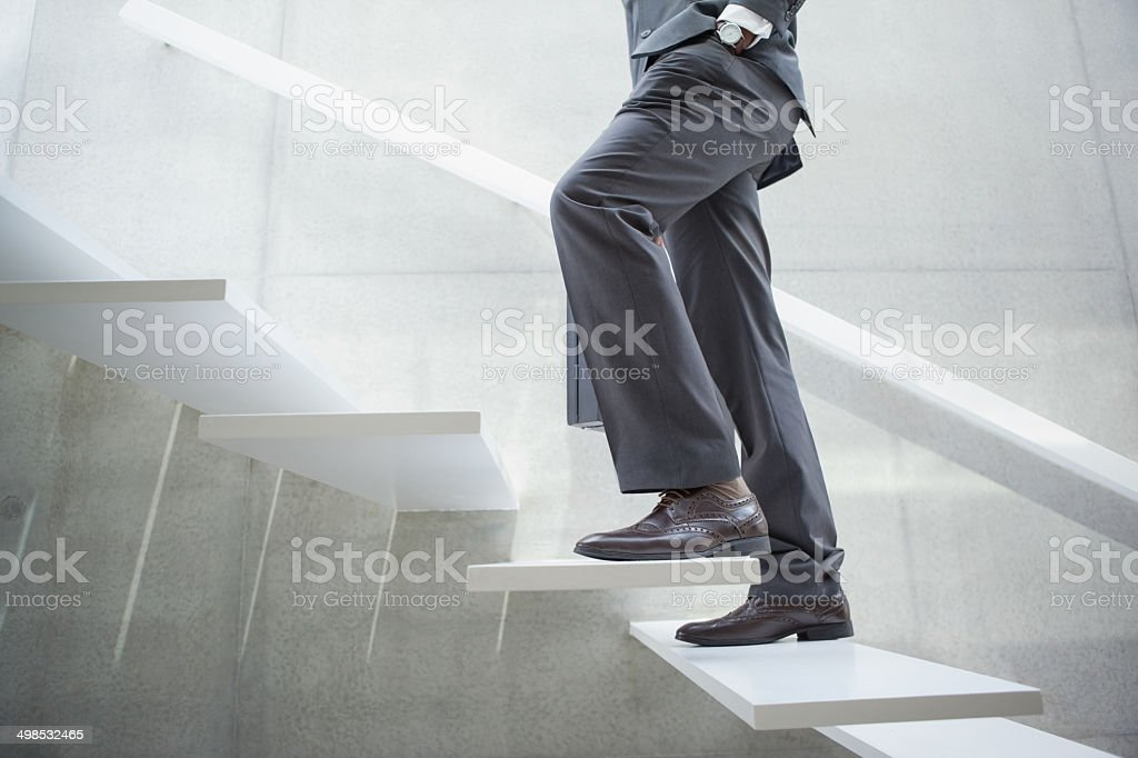 Businessman walking up the stairs stock photo