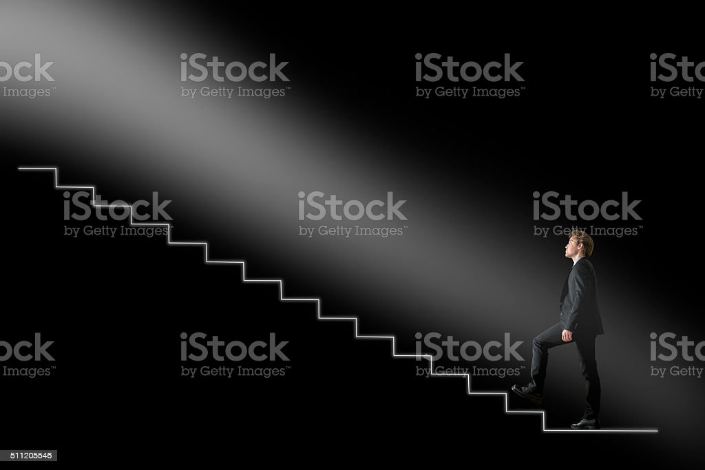 Businessman walking upwards towards the light on conceptual stai stock photo