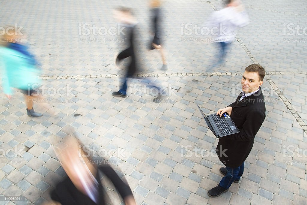A businessman walking while carrying his laptop royalty-free stock photo