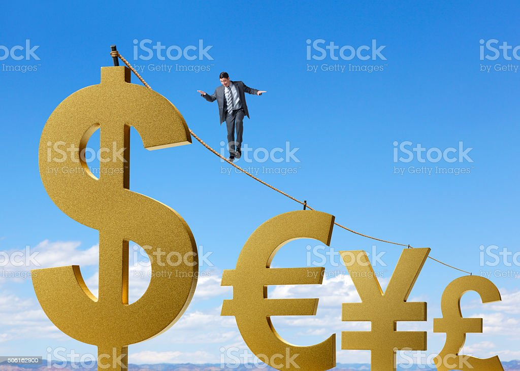 Businessman Walks On Tightrope Between Major Currency Symbols stock photo