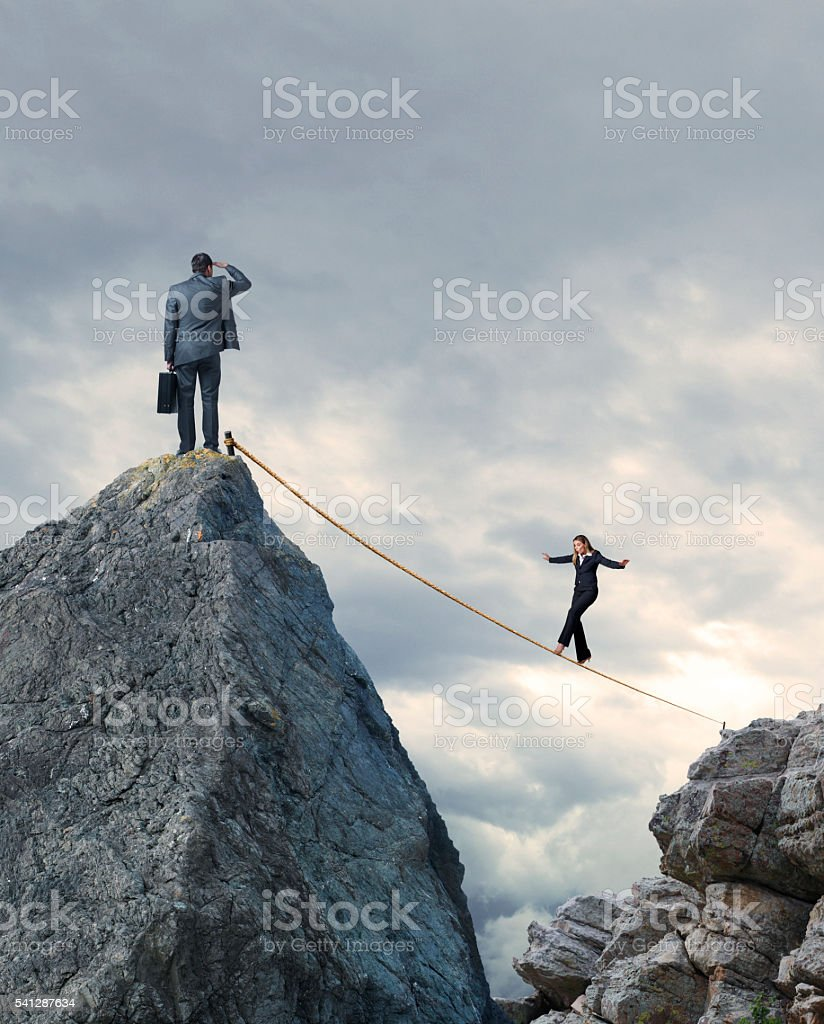 Businessman Watching Businesswoman Walk A Tightrope stock photo