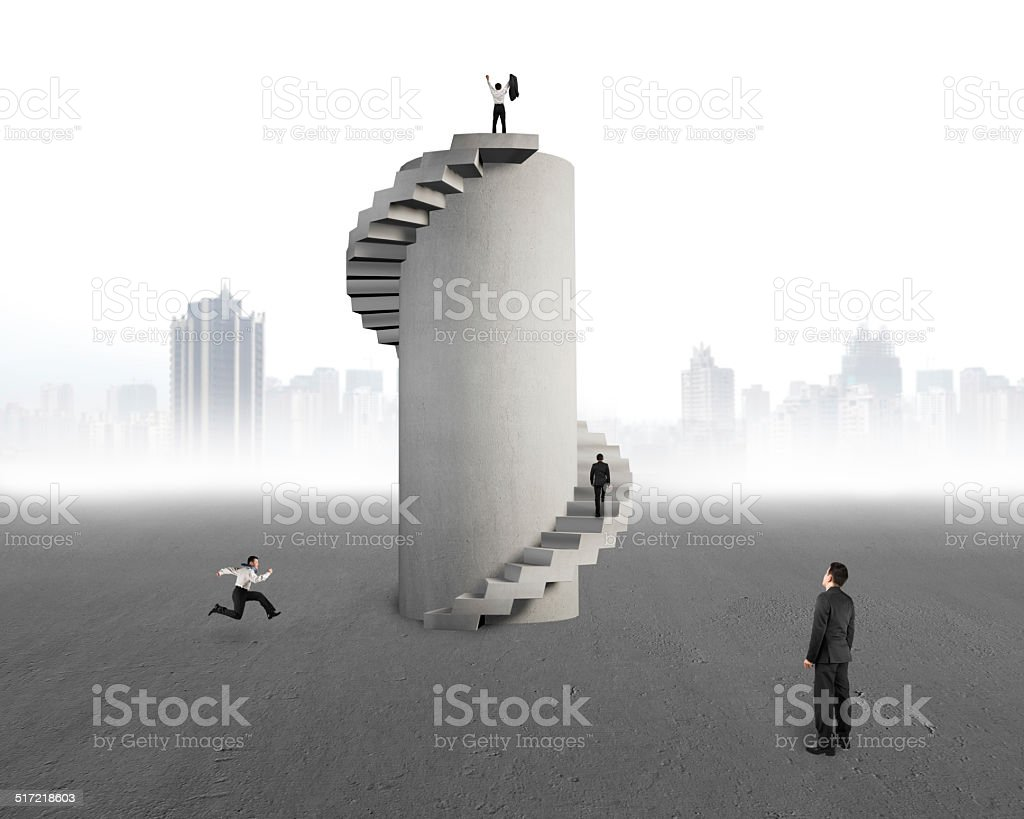 businessman watching men with concrete spiral tower stock photo