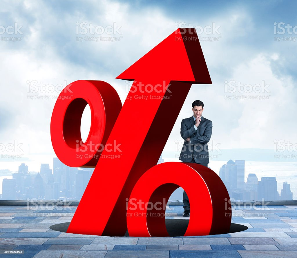 Businessman Watching Rising Interest rates Emerging From Hole stock photo