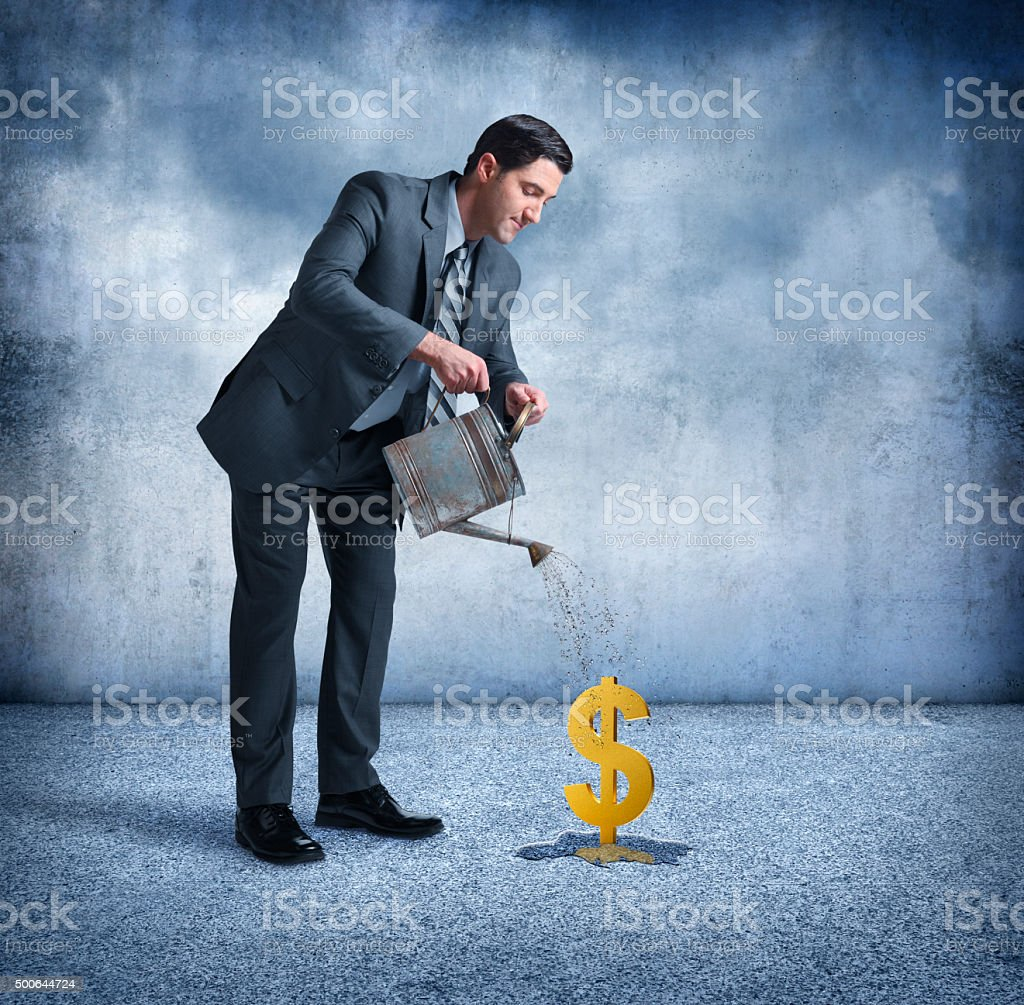 Businessman Watering A Dollar Sign stock photo