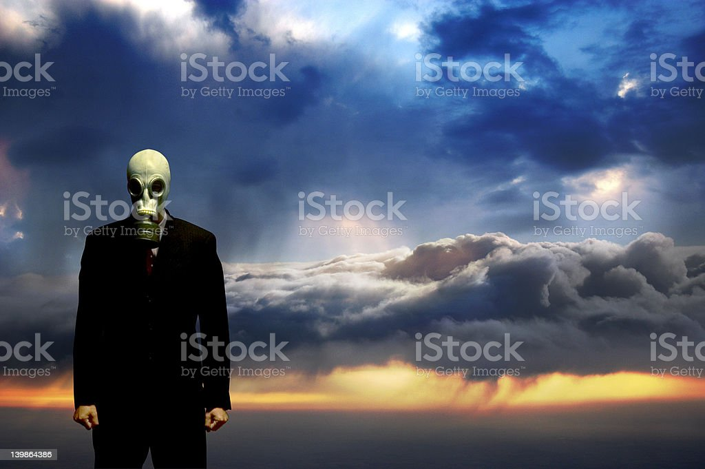 Businessman wearing a gas mask with clouds in the background royalty-free stock photo