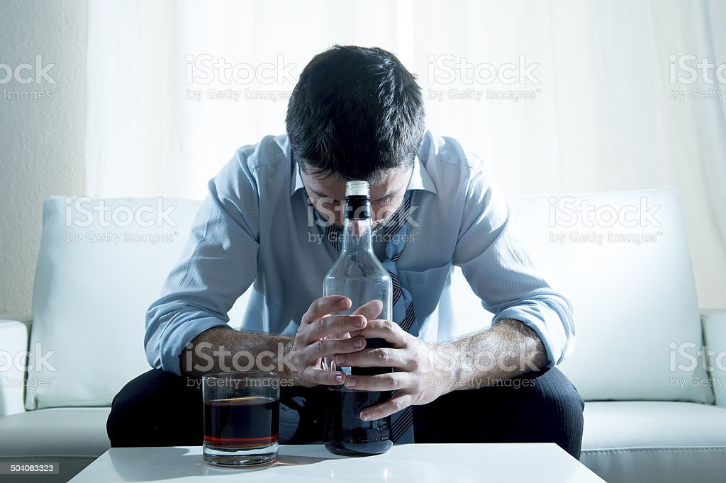 Businessman wearing blue shirt drunk at desk on white background stock photo