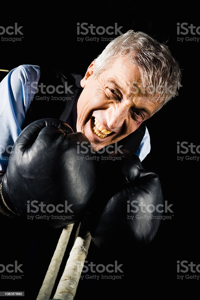 Businessman Wearing Boxing Gloves and Standing in Ring stock photo