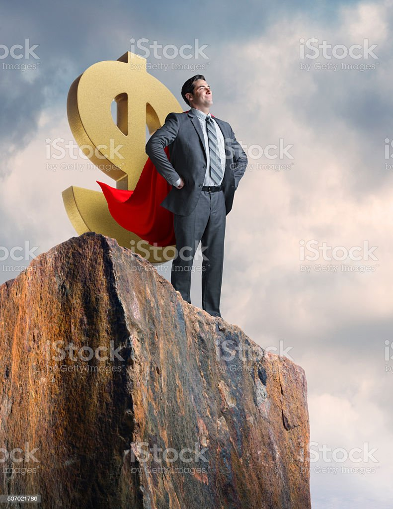 Businessman Wearing Cape Stands Cofidently While Protecting Dollar Sign stock photo