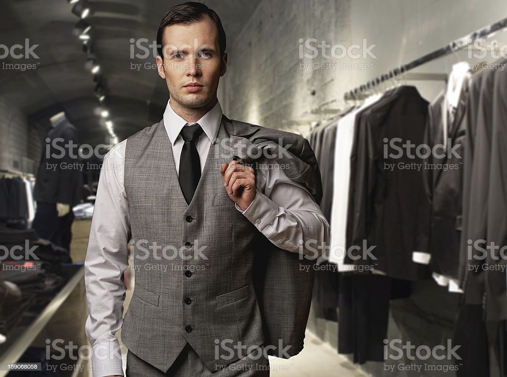 Businessman wearing classic vest against row of suits in shop stock photo