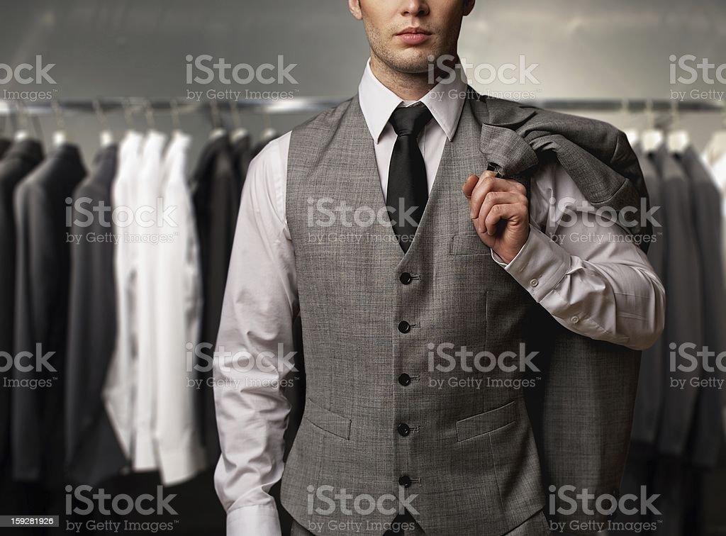 Businessman wearing classic vest against row of suits in shop royalty-free stock photo