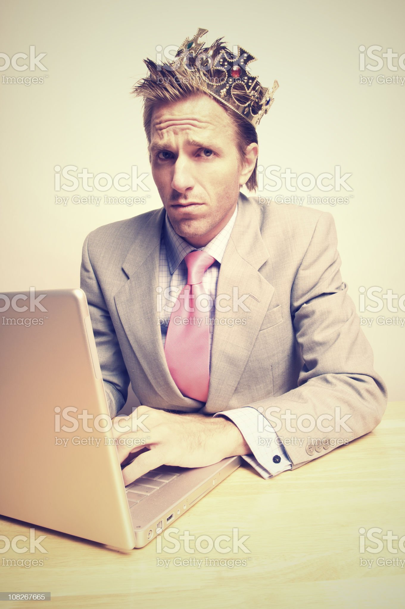 Businessman Wearing Crown and Working on Laptop royalty-free stock photo