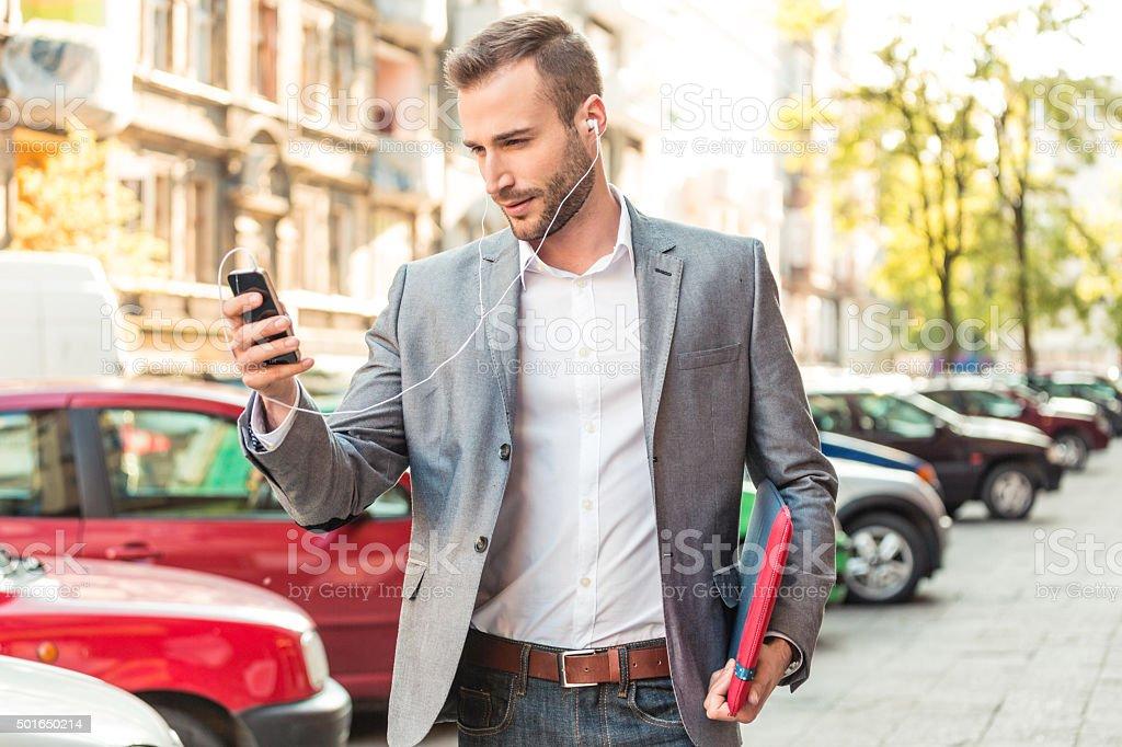 Businessman wearing earphone talking on smart phone on the street stock photo