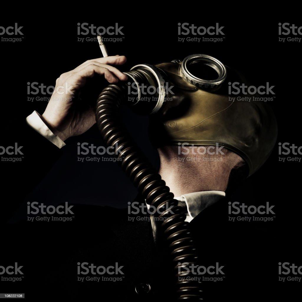 Businessman Wearing Gas Mask and Smoking Cigarette stock photo