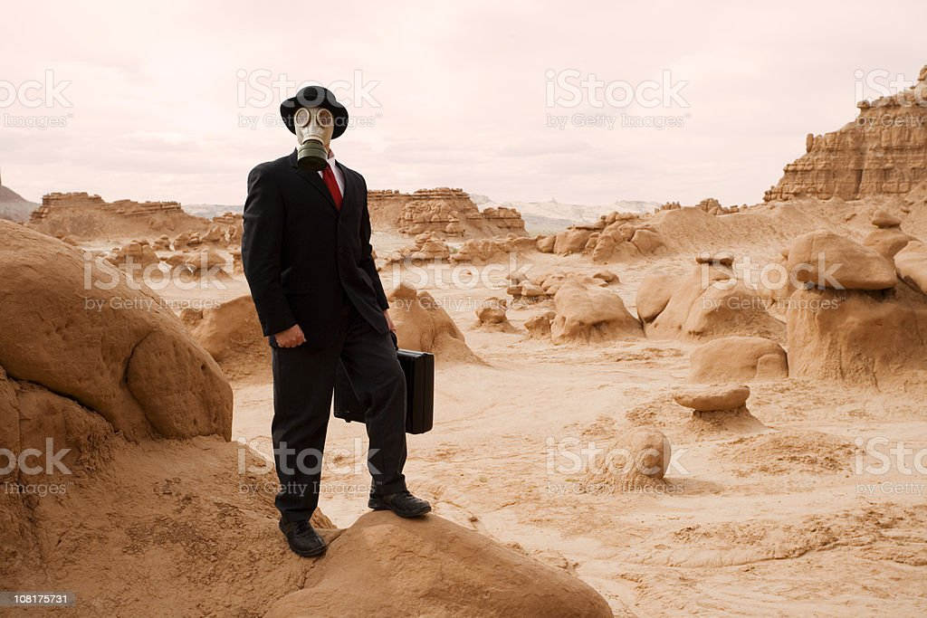 Businessman Wearing Gas Mask in Barren Landscape royalty-free stock photo