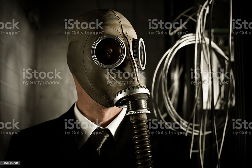 Businessman Wearing Gas Mask in Dark Server Room stock photo