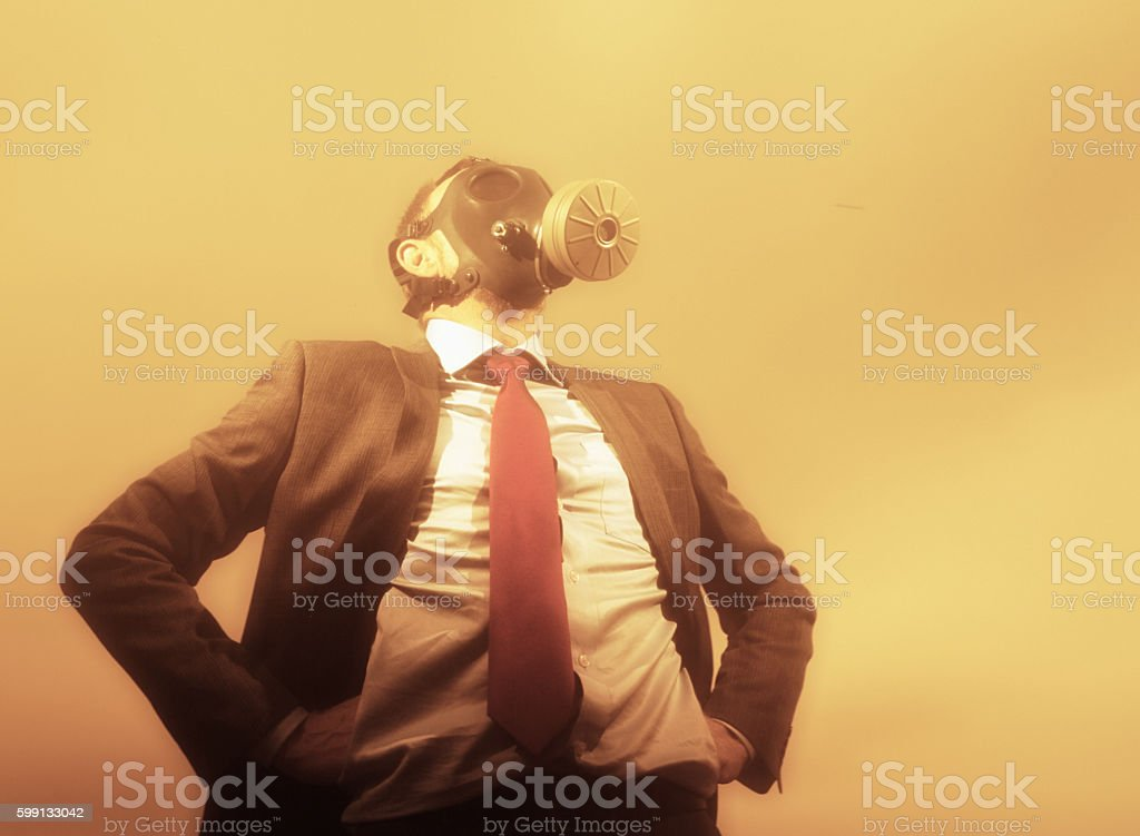 Businessman wearing gasmask to protect him from smoggy, polluted air stock photo