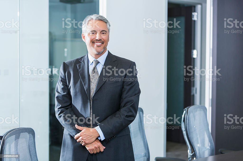 Businessman wearing gray suit standing in office stock photo