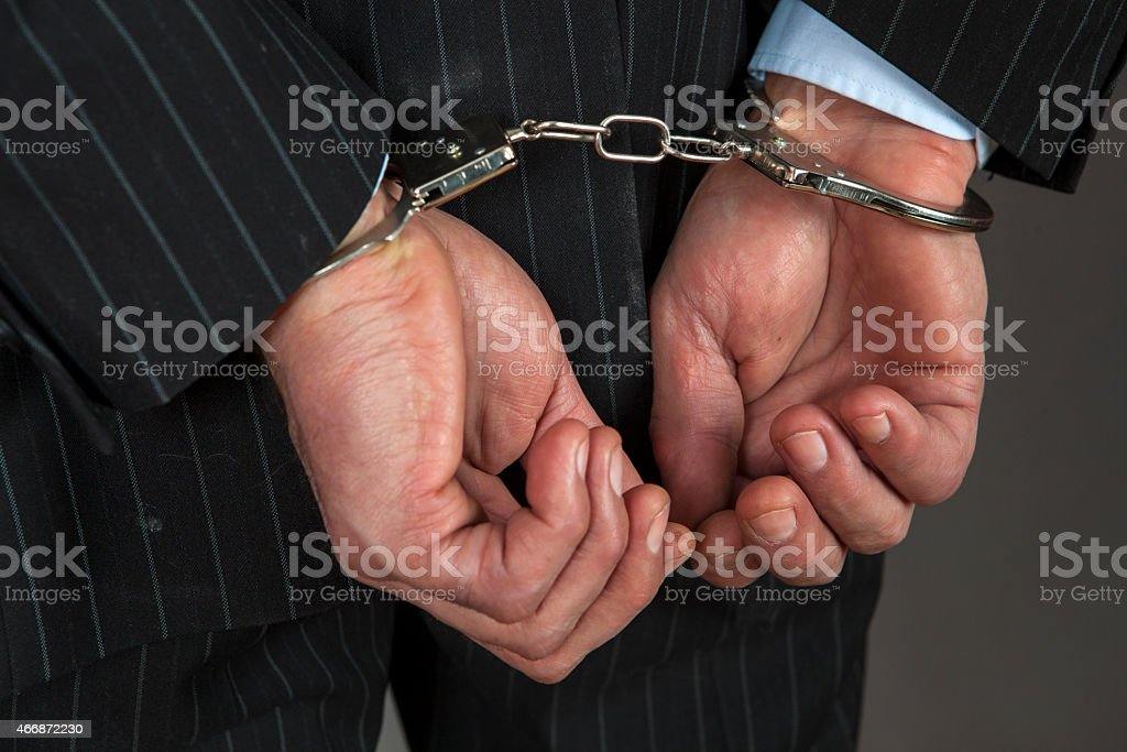 A businessman wearing handcuffs stock photo