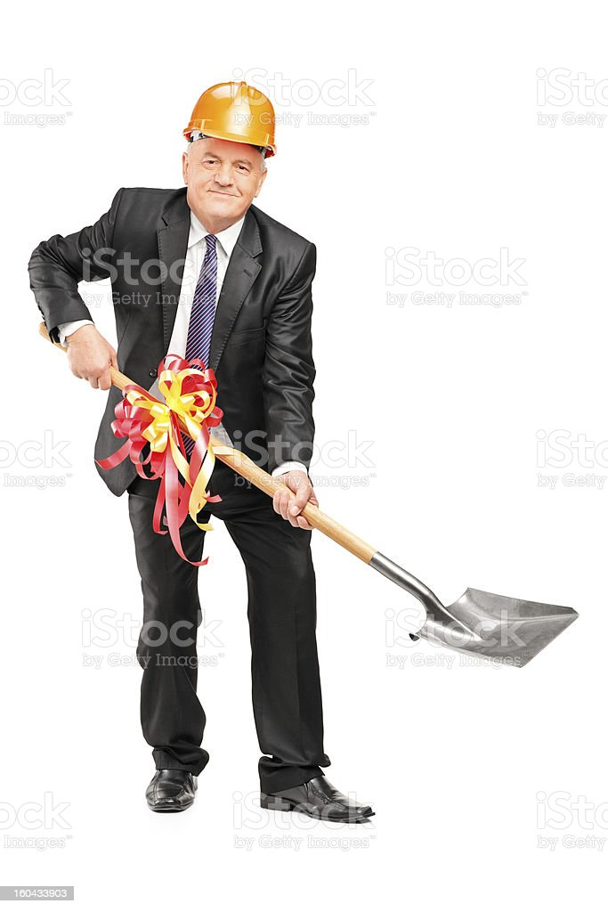 Businessman wearing helmet and holding a shovel with ribbon stock photo