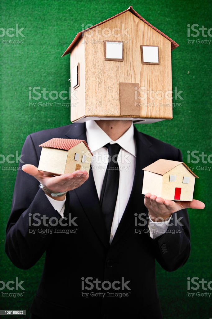 Businessman Wearing House as Mask Holding Two Similiar Houses royalty-free stock photo