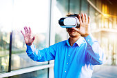 Businessman wearing VR glasses and enjoys fun