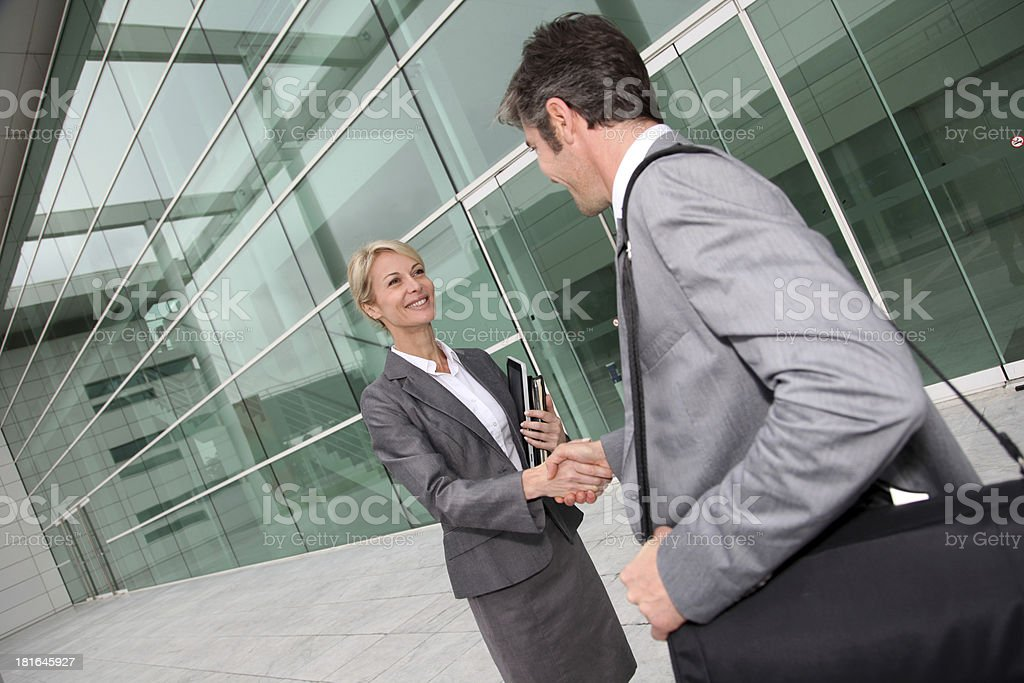 Businessman welcoming client in front of building stock photo