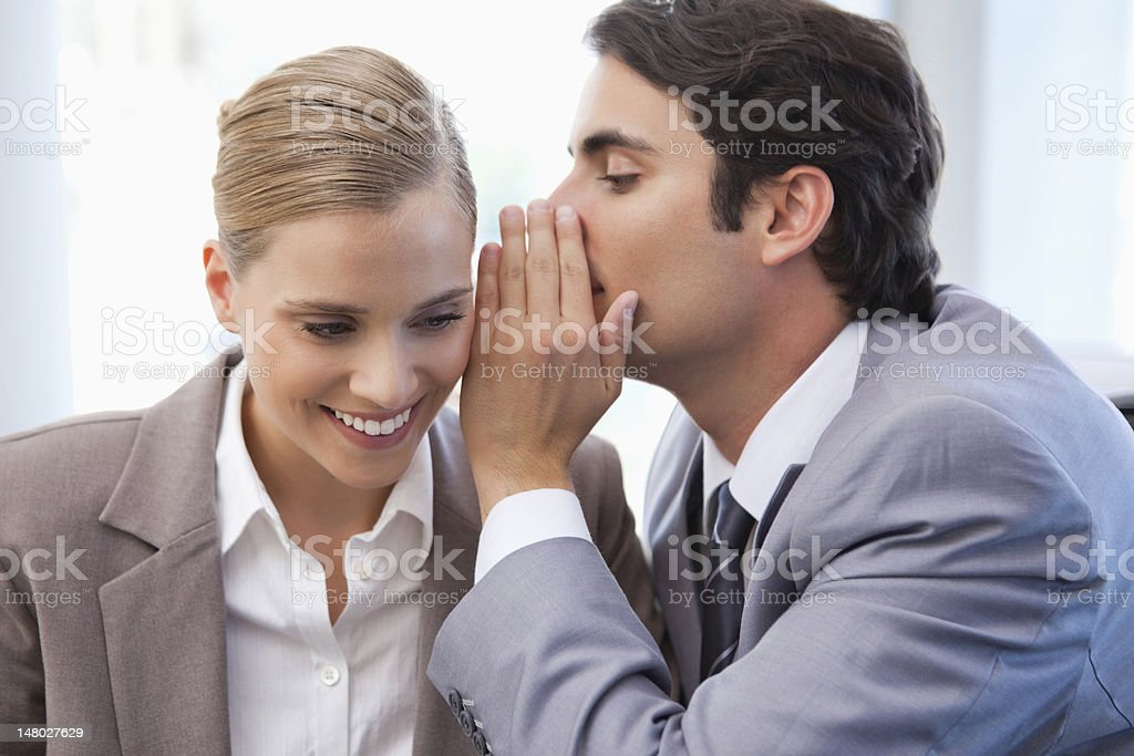 Businessman whispering something to his colleague stock photo