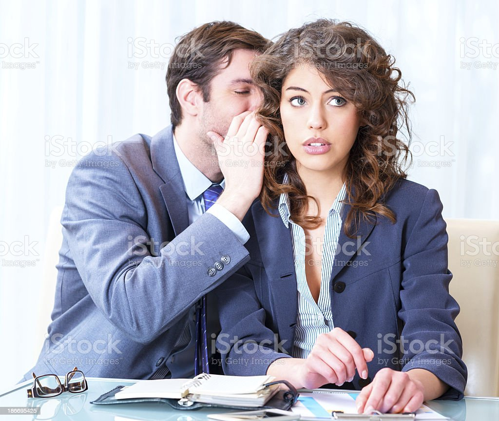 Businessman whispering something to his colleague royalty-free stock photo