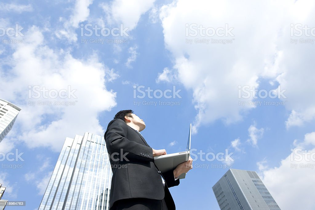 Businessman who looks up at the sky stock photo