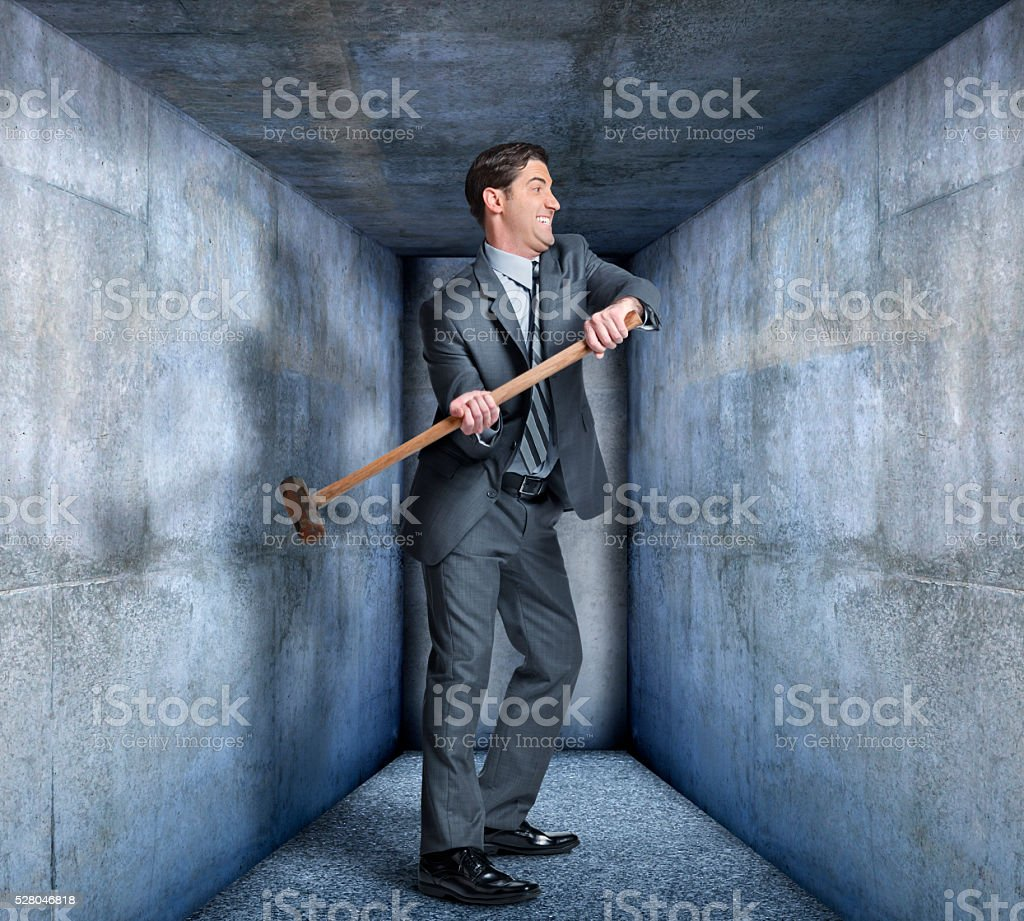 Businessman Wields Sledgehammer To Break Out Of Confinement stock photo