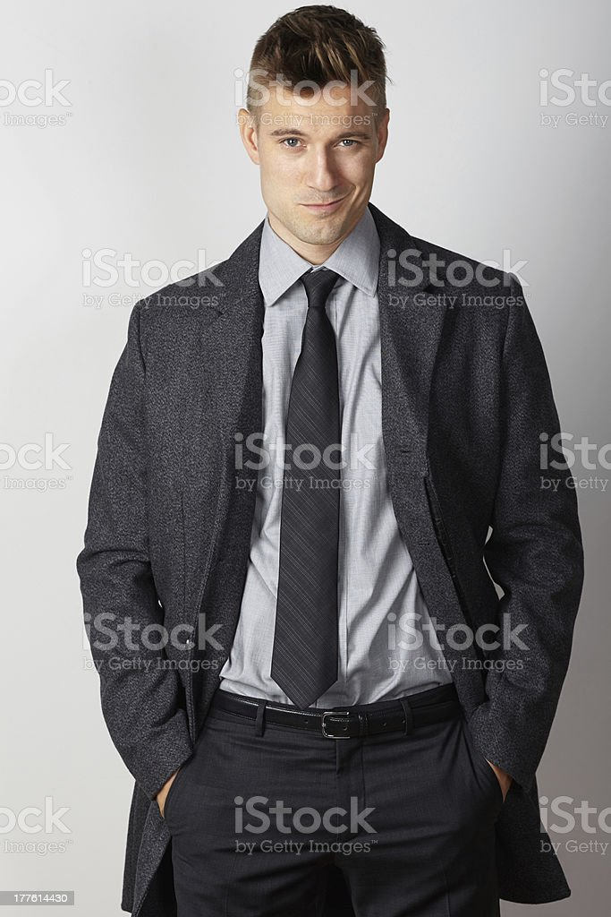 Businessman winter coat smiling hands in pockets royalty-free stock photo