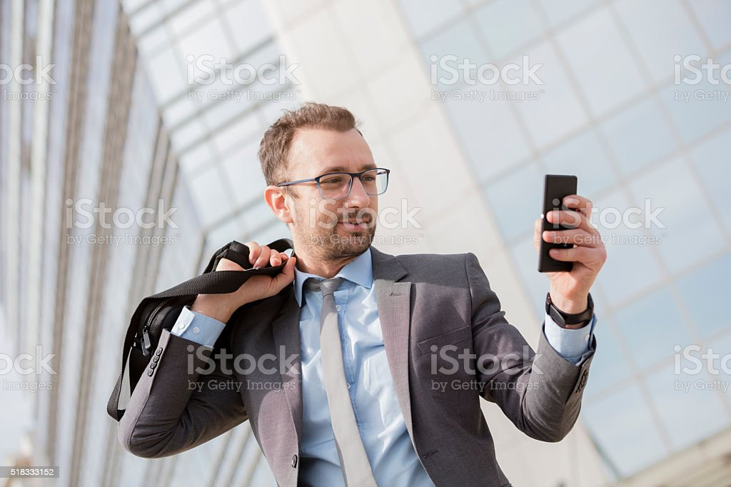 Businessman with a bag over his shoulder using smart phone stock photo