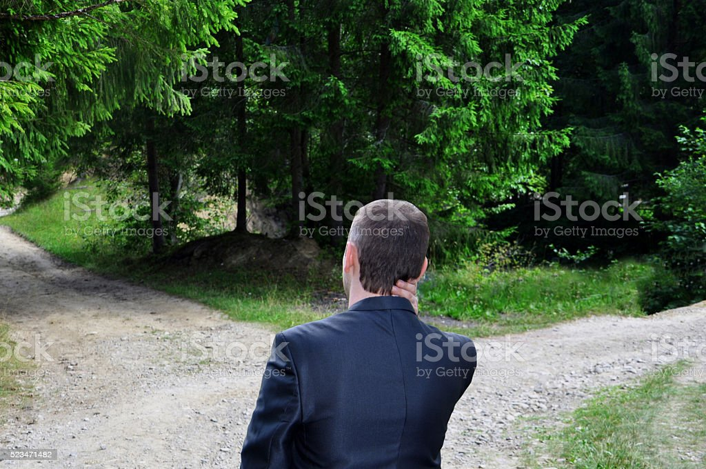 businessman with a choice near the forked road stock photo
