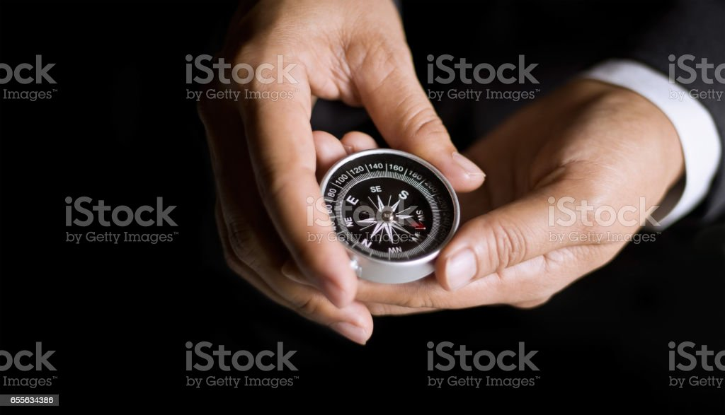 Businessman with a compass holding in hand on dark background stock photo