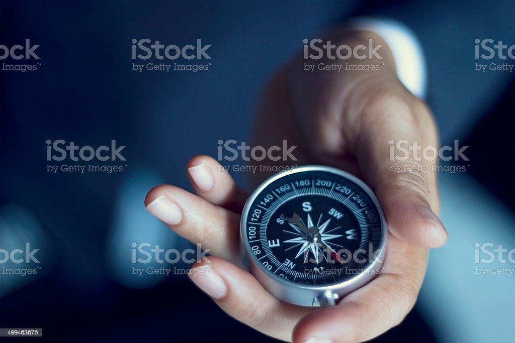 Empresário com uma bússola segurando na mão - fotografia de stock