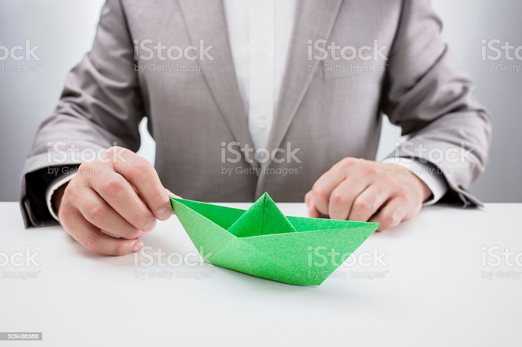 Businessman with a green paper boat stock photo