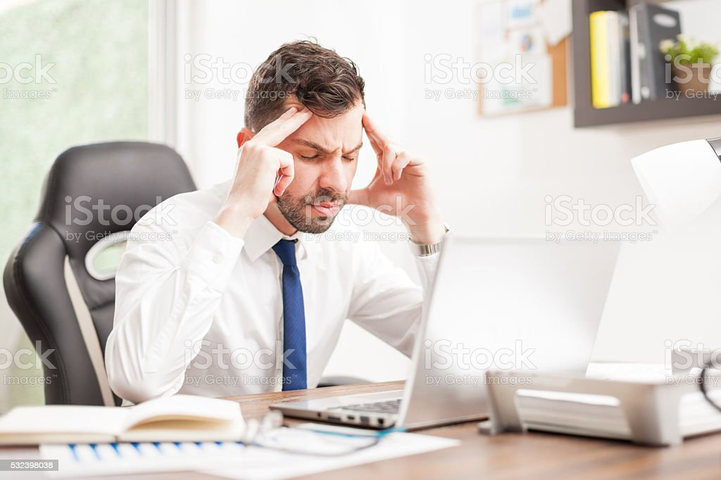 Businessman with a headache in an office stock photo