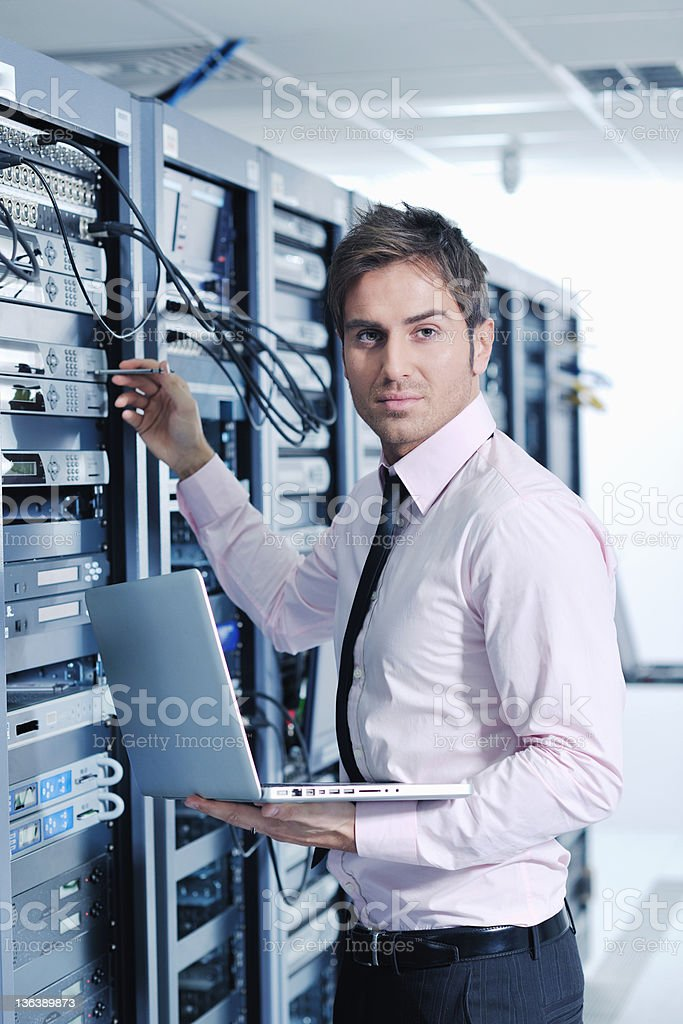 Businessman with a laptop working in a network server room royalty-free stock photo