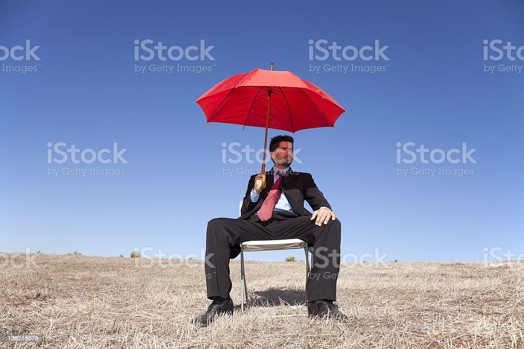Businessman with a red umbrella royalty-free stock photo