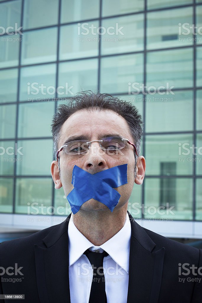 Businessman with Adhesive Tape Over Mouth stock photo