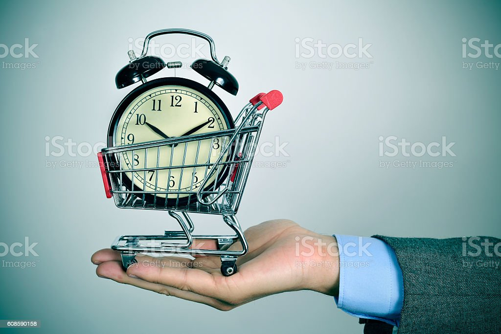 businessman with an alarm clock in a shopping cart stock photo