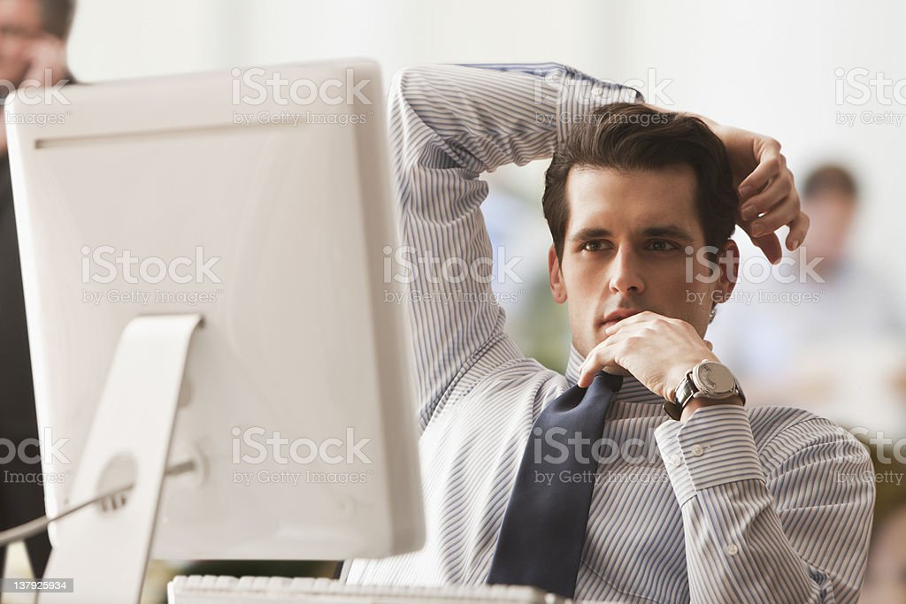 Businessman with arm over his head stock photo