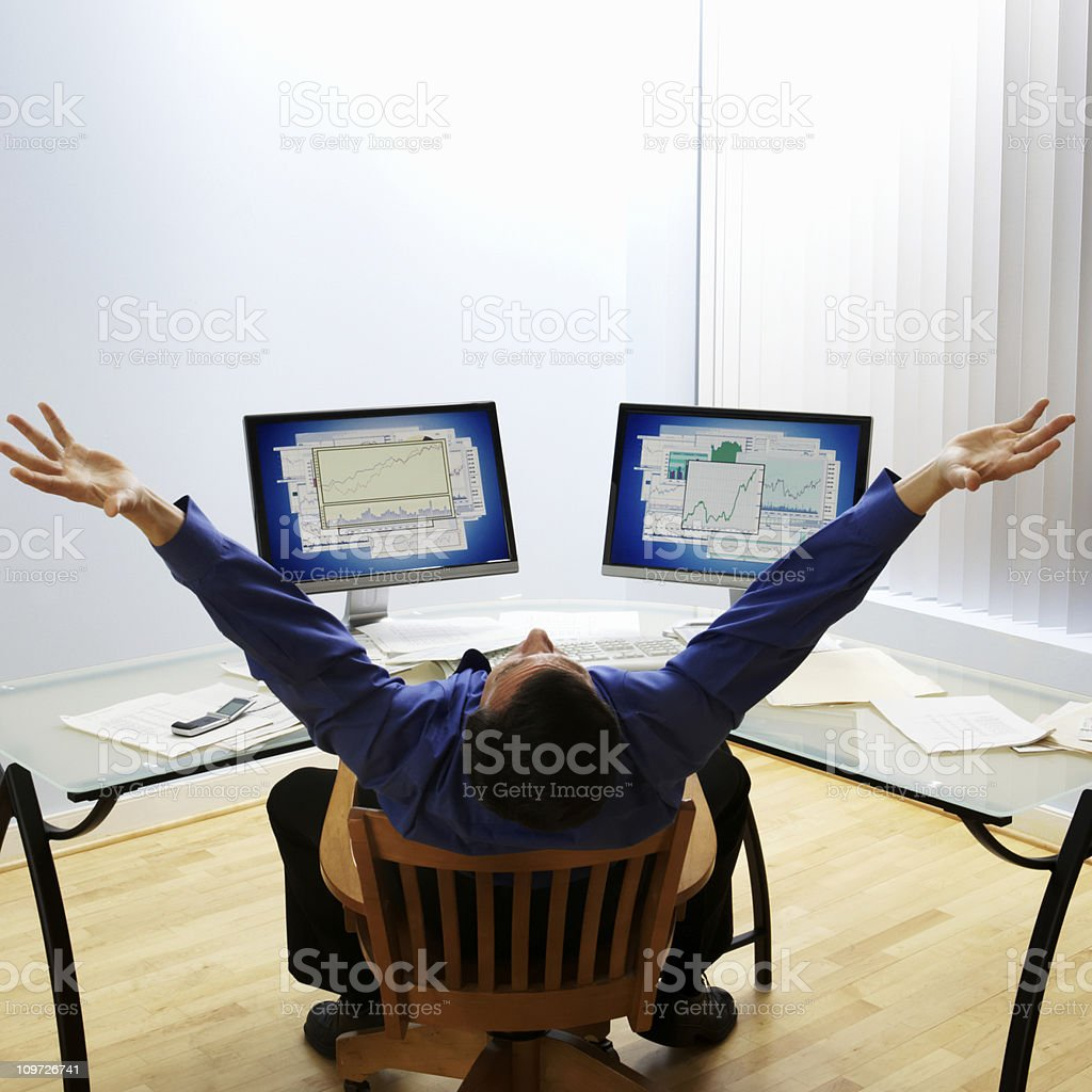 Businessman with Arms Raised at Desk royalty-free stock photo