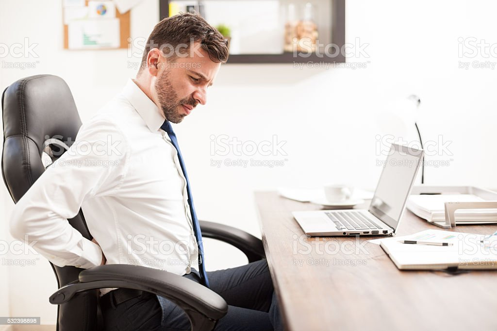 Businessman with back pain in the office stock photo